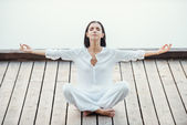 Woman in white clothing sitting in lotus position — Stock Photo