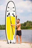 Man holding his paddleboard — Stock Photo