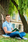 Confident student reading book  on the grass — Stock Photo