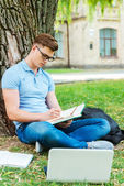 Student in glasses writing something in his note pad — Foto Stock