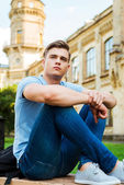 Student sitting on the bench and looking away — Stock Photo