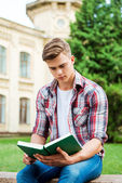 Student reading book while sitting on the bench — Stock Photo