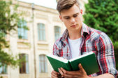 Student reading book against the university building — Stock Photo