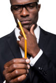 African man in formalwear holding pencil — Stock Photo