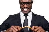 African man in formalwear breaking pencil — Stock Photo