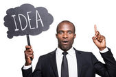 African man in formalwear holding banner with text IDEA — Stock Photo