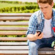 Man holding rose and looking at his mobile phone — Stock Photo #51475065