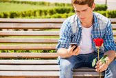 Man holding rose and looking at his mobile phone — Photo