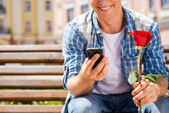 Man holding rose and mobile phone — Stock Photo
