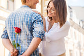 Is it for me? Rear view of young man holding red rose behind his back while woman walking in the background — Stock Photo