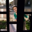 Housewife looking through glass door — Stock Photo #36031873