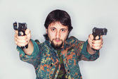 Determined criminal holding two guns — Stock Photo