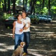 Pregnant couple with puppy in a forest — Stock Photo