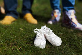Baby shoes in front of future parents — Stock Photo