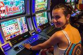 Smiling woman playing slot machines — Stock Photo