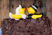 Rubber ducks sitting on the chocolate cake as cake toppers for a wedding ceremony and reception — Stock Photo