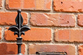 Part of an iron gate against red brick wall — Stock Photo
