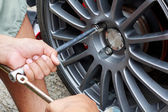 Mechanic hands with tool repairing the car at garage. — Stock Photo