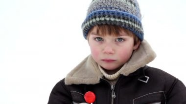 Boy in winter eating a lollipop, boy eating candy,boy licks lollypop,emotional boy, — Stock Video
