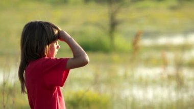 Boy on a flooded meadow, swamp boy explores, wild nature — Vidéo