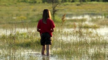 Boy on a flooded meadow, swamp boy explores, wild nature — Vídeo Stock