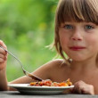 图库视频影像: Boy eating vegetables, boy with appetite eats healthy food outdoors