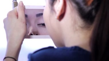 Young woman doing makeup in front of a mirror, full face, blurred background.Beautiful  young girl is doing makeup.Young woman with mirror and makeup brush. — Stock Video