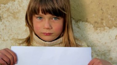 Boy holding a sheet of paper.Child holding a sheet of paper.Against the background of an old wall — Stock Video
