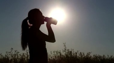 Young woman drink water at sunset.Girl drinks water from a bottle (banks) — Stock Video