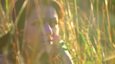 Portrait of beautiful girl, sitting in the grass.Girl in a field at sunset (close-up portrait) — Stock Video