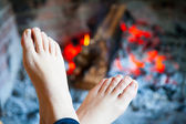 Feet are heated in the fire place — Stock Photo