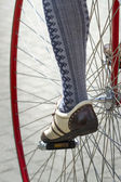 Close up of a velocipede wheel with the fragment of a cyclist's leg in beautiful oldfashioned wear — Stock Photo