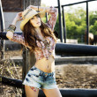 Brunette young girl posing in country hat. — Stock Photo