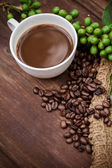 Cup coffee and beans on wood background — Stock Photo