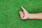 Hand with thumb up on green grass background texture — Stock Photo