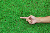 Human hand point with finger on green grass background texture — Stock Photo
