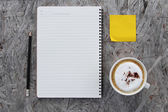 Cup of coffee and notebook paper on a wooden table — Stock Photo