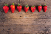 Fresh strawberries on old wooden background — Stock Photo