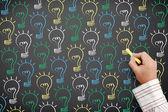 Drawn light bulbs on blackboard — Stock Photo