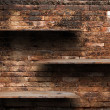 Empty wood shelves on old brick wall background, grunge industrial interior Uneven diffuse lighting version. — Foto Stock