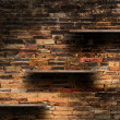 Empty wood shelves on old brick wall background, grunge industrial interior Uneven diffuse lighting version. — Stock Photo #42385525
