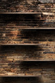 Empty wood shelves on old brick wall background, grunge industrial interior Uneven diffuse lighting version. — Stock Photo