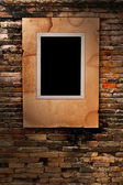 Old paper photo frame on old brick wall texture — Stock Photo