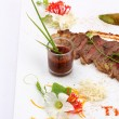 Beefsteak decorated with edible flowers — Stock Photo