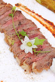 Beefsteak decorated with edible flowers — 图库照片