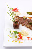 Beefsteak decorated with edible flowers — Stok fotoğraf