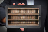Tablet computer in businessman hand with wood shelves — Zdjęcie stockowe