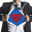 Businessman showing a superhero suit underneath heart beat symbol — Stock Photo #49981003