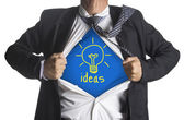 Businessman showing a superhero suit underneath idea light bulb symbol — Stock Photo