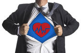 Businessman showing a superhero suit underneath heart beat symbol — Stock Photo
